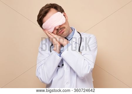 Young Caucasian Male Doctor With Sleeping Mask On Eyes Resting Having A Nap.