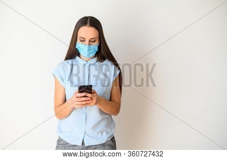 Protect Yourself From Epidemic, Communicate Remotely. A Young Woman In A Medical Mask On Her Face Is