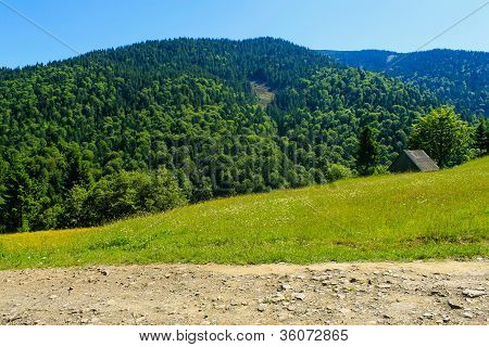 Wooden House And Road In Mountains