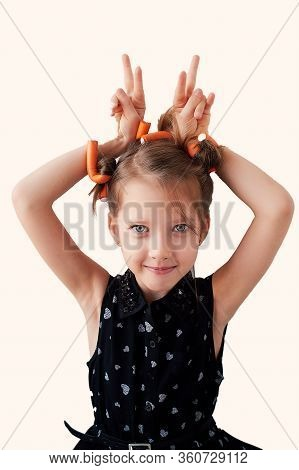A 6-year-old Girl With Curlers On Her Head, Fooling Around. The Pursuit Of Beauty. Childrens Joys. I