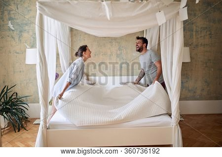 Couple making bed.Charming smiling man and woman in love making bed together.