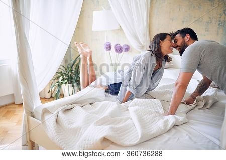 Happy woman and  man  enjoying intimate moment at morning in bed.
