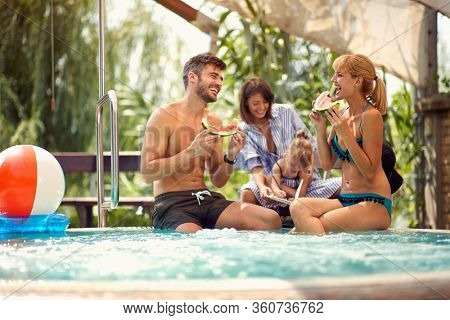 Couple with child and babysitter eats water melon on pool