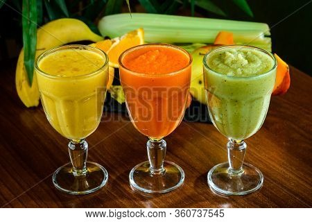 Healthy Vegetable And Fruit Juices Or Smoothie In Glass, Ripe Slices Of Orange, Apple, Carrot, Celer