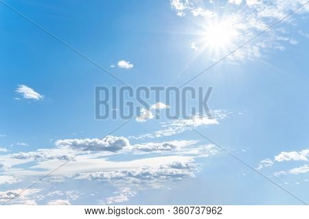 Sun With Sunrays On The Blue Sky With White Clouds. Daytime And Good Weather