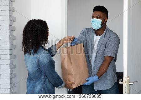 Food Delivery During Coronavirus. Black Courier Guy Wearing Medical Mask Delivering Grocery Order To