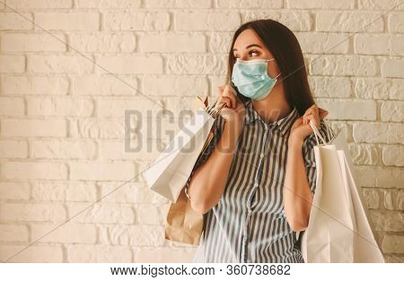 Young Happy Woman Shopaholic In Medical Face Mask Hold Shopping Bags And Looking At Copy Space. Beau