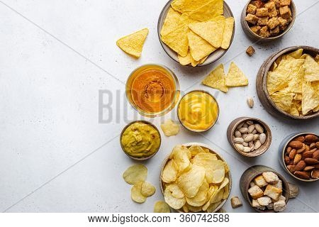 Veraity Bowls Of Beer Snacks And Sauces On Stone Table. Nuts, Chips, Nachos, Crackers. Top View With