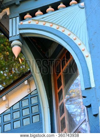 Beautiful Wooden Trim On Victorian Home Has Spindles And Elaborate Cuts.  Woodwork Is Painted In Fiv