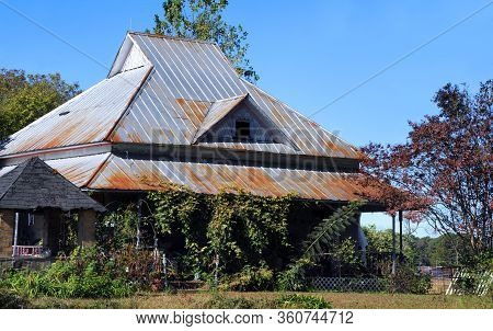 Old Home Has An Unusual Cut To Its Roof Line. Tin Covers Roof With Russt Beginning To Set In.  Well