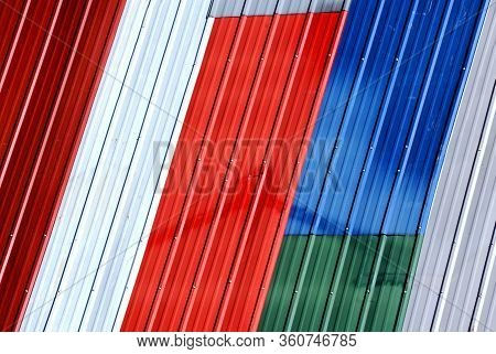 Unique Shed Roof Is Covered In Multiple Colors Of Tin Roofing.  It Looks Like A Patchwork Tin Quilt.