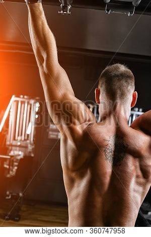 The Athlete Does A Pull-up On The Horizontal Bar. A Man In Great Shape Is Doing Pull-ups On The Hori