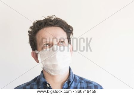 Frontal Portrait Of A Young Man Looking Up, Wearing A Disposable Face Mask, To Prevent The Spread Of