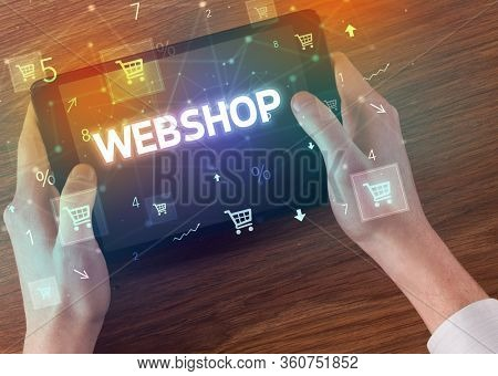 Close-up of a hand holding tablet with WEBSHOP inscription, online shopping concept