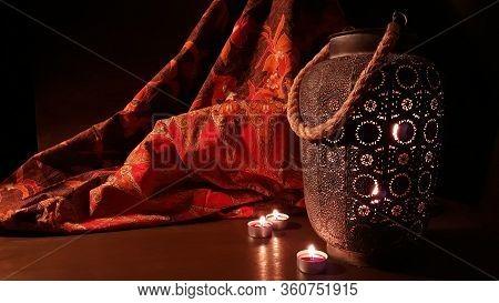 Arabian Lantern Near A Red Oriental Fabric On A Brown Wooden Background.eid Lamp Or Lantern For Rama