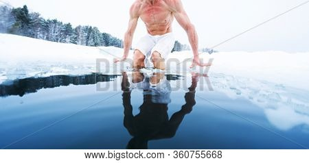Young athletic man going to have ice bath in the winter pond