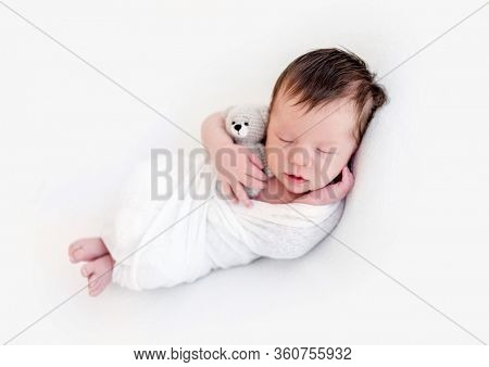Adorable newborn in white blanket holding toy in tiny hand
