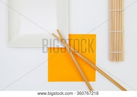 Top View Of White Empty Sushi Plates With Bamboo Chopsticks. Symmetry Food Design