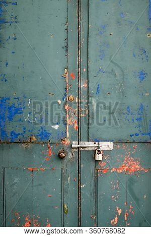 Paint Flaking Off A Disused Locked Up Door With Padlock And Grungey Bright Colors