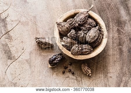 Black Cardamom In A Bowl On Wooden Background Top View