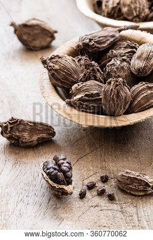 Black Cardamom In A Bowl On Wooden Background