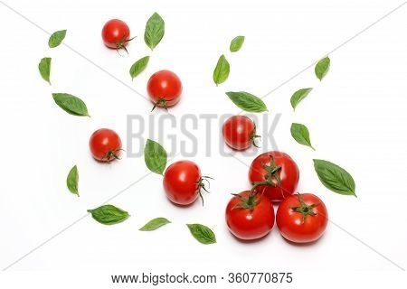 Truss Tomatoes And Basil Leaves On White Background