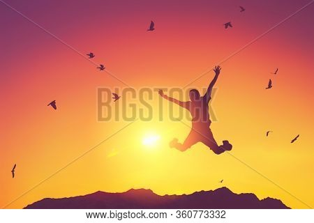 Silhouette Man Jump And Birds Fly On Sunset Sky And Cloud Texture Abstract Background.