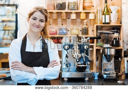 Young Woman In Brown Apron Is Ready To Take Order From Client Customer In Cafe, Restaurant. Smiling