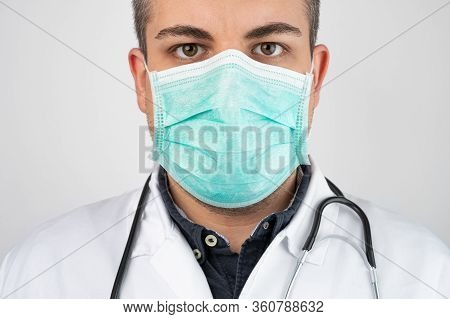 Caucasian Man Posing As A Medical Doctor In White Overall Or Scrub With Protective Face Mask And Ste