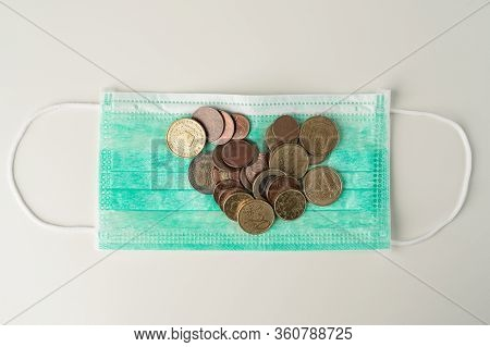 Euro Coins Lying On Green Protective Face Mask. Medical Treatment Or Pandemic Costs And Expenses Abs