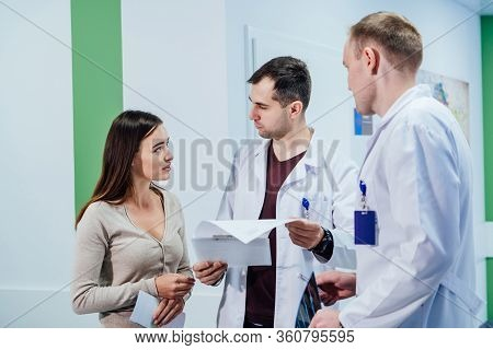 Discussing Medical Issues. Patient Discuss With Doctors On Her Medical Exam At Hospital. Doctors Tal