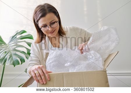Mature Woman Unpacks Cardboard Box On Table At Home, In Office. Service For International Postal Del