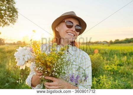 Outdoor Portrait Of Mature Happy Smiling Woman With Spring Flowers, Female In Sunglasses Hat, Golden