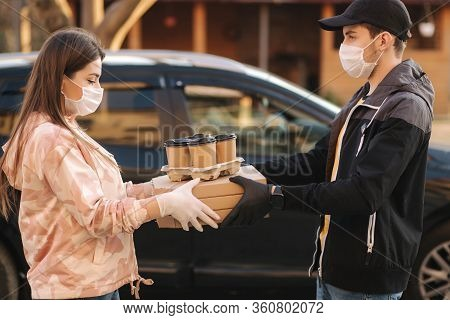 Young Woman In Protective Mask And Medical Mask Take Order From Delivery Boy Outside. Food Delivery
