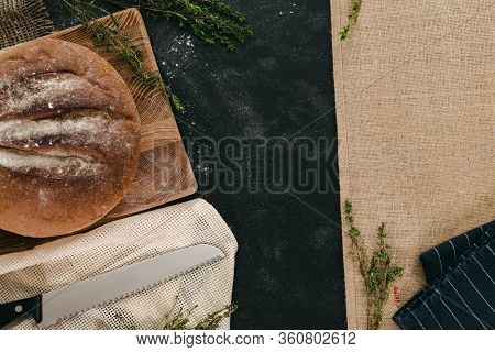 Loaf Of Bread With Canvas And Thyme On Black Background. Bulletin Board Concept With Copy Space.