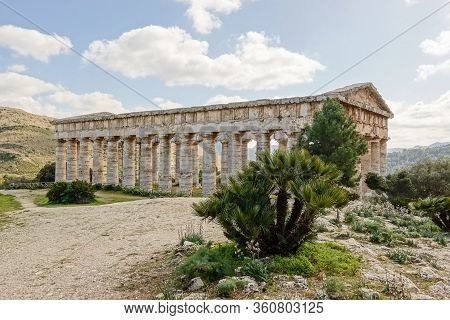 Ancient Doric Temple Of Segesta Hidden Behind The Trees In Nice Sunny Spring Day In Sicily, Italy