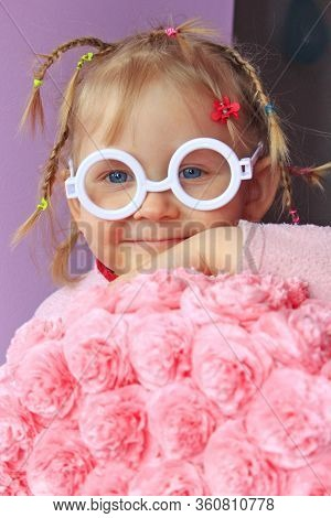 Little Girl In Plastic Glasses Smile Near Paper Flowers Made From Papier-mache. Portrait Of Baby Wit