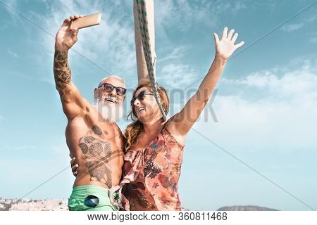 Senior Couple Taking Selfie With Mobile Smartphone On Sailboat Vacation - Happy Mature People Having