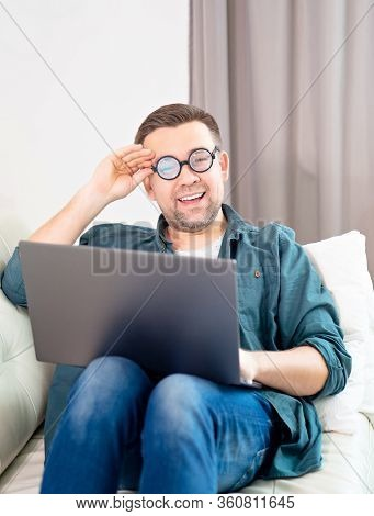 Male Freak With Glasses, Blogger, Freelancer, Businessman Working Online Lying On The Couch. Stay Ho