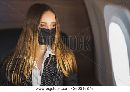 A Beautiful Young Blonde Woman In A Stylish Business Suit Sits On A Private Plane In A Black Medical