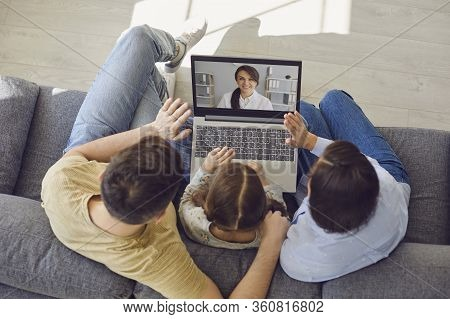 Family Doctor Online. Family Talking Consults A Doctor Using A Laptop While Sitting At Home On The C