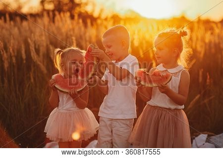 Happy Kids Eating Watermelon. Kids Eat Fruit Outdoors. Healthy Snack For Children. Little Girls And