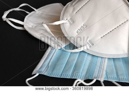 white KN95 or N95 mask with antiviral medical mask for protection against coronavirus on black backg