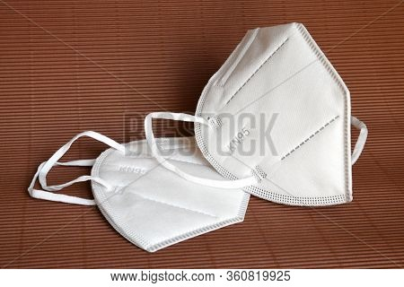 White Kn95 Or N95 Mask For Protection Against Coronavirus On Brown Background. Surgical Protective M