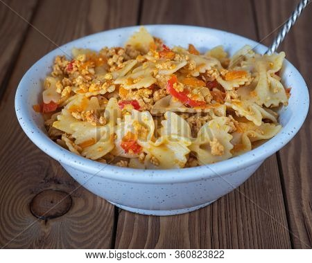Pasta With Chicken And Pepper Lived In A Deep Plate On A Wooden Tray With A Spoon On A Wooden Tray
