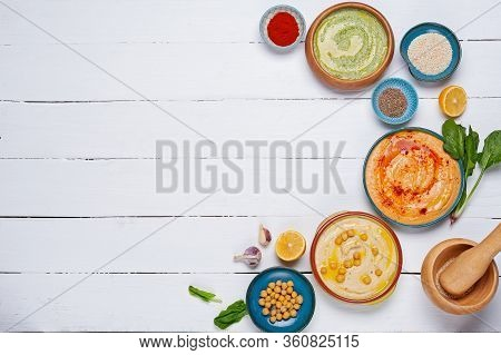 Colorful Hummus Bowls, Healthy Vegan Dips On A White Wooden Background. Hummus With Spinach, Paprika
