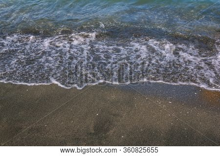 View Of The Beach With Sea Clear Water Waves And Black Volcanic Sand. Natural Phenomenon.
