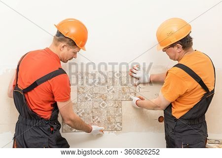 Workers Are Trying On The Ceramic Tile On The Wall.