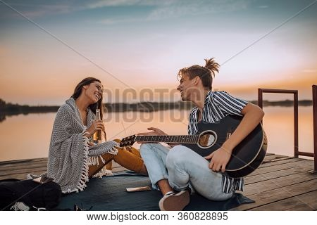 Young Couple Drinking Beer, Playing A Guitar And Singing While Sitting On A Wooden Pontoon Near A Ri