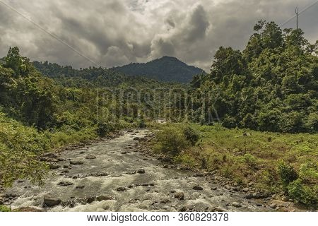 Wild Clean River Scene In Lush Forest Seen On A Cloudy Day With Haze In Jambi Province, Sumatra, Ind